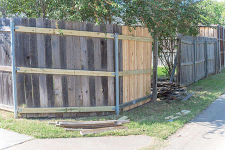 Concrete back alley with old fence near new lumber boards pickets at suburban residential house in Texas, USA Imagens