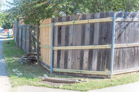 Aged wooden fence near new lumber boards installation of suburban residential house in Texas, USA