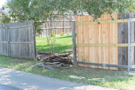 Concrete back alley with old fence near new lumber boards pickets at suburban residential house in Texas, USA Foto de archivo