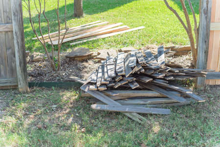 Pile of aged fencing panels near new lumber boards fence of suburban residential house in Texas, USA