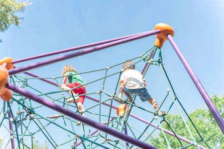Upward view of multiethnic diverse kids on climbing dome at playground near Dallas, Texas, USA Imagens