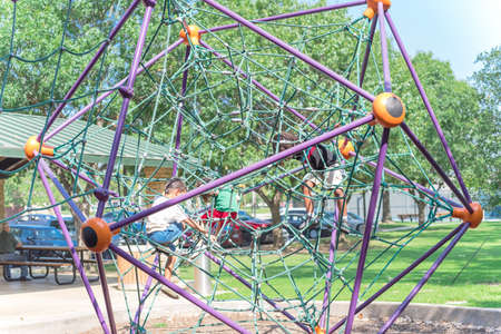 Diverse kids climbing the web net at playground near Dallas, Texas, USA close-up view