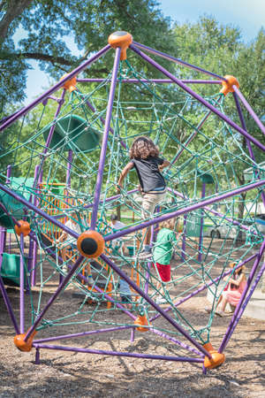 Multiethnic children climbing the web net at playground near Dallas, Texas, USA nature park
