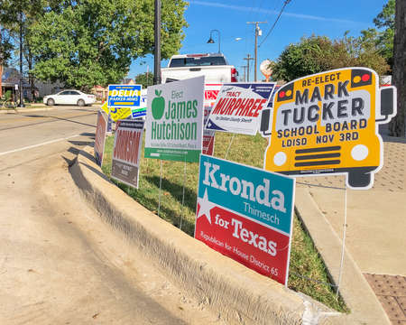Row of election poster and campaign yard sign near an early voting location in main street Roanoke, Texas