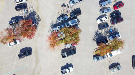 Grocery store parking lot with shopping carts return area surrounded by colorful autumn leaves in suburban Dallas, Texas, America
