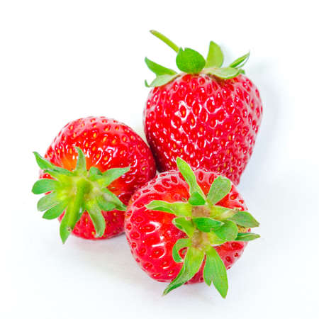Three strawberries isolated on white background with copy space and clipping path. Fresh harvested homegrown strawberry fruit. Imagens