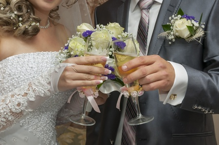 Wedding champagne in hands of the groom and the bride against a bouquet photo