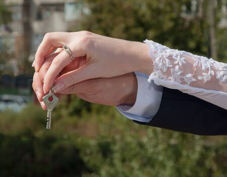 wedding customs: Hands of bride and groom hold the key Wedding customs Stock Photo