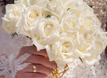 wedding ring hands: Wedding bouquet of roses in hand of the bride