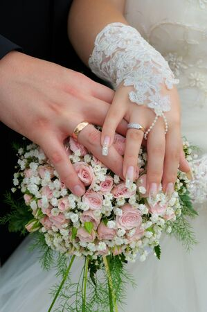 A newly wed couple place their hands on a wedding bouquet showing off their wedding bands  photo
