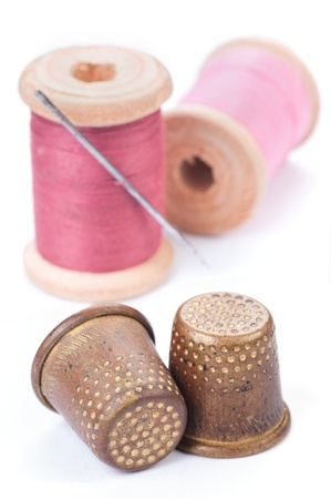 Old thimbles and needle with pink thread on white with shadow