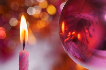 A candle on the background of Christmas decorations photo