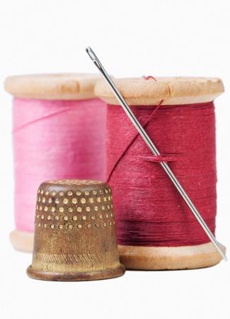hilo rojo: Antiguo dedal y aguja con hilo de color rosa y rojo sobre fondo blanco con la sombra