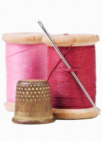needle and thread: Old thimble and needle with pink and red  thread on white with shadow