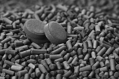 Activated carbon granules and tablets close up Archivio Fotografico