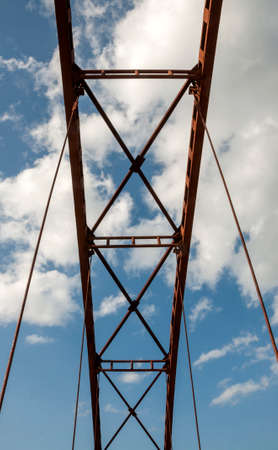 pedestrian bridges: The design of the old iron bridge on the background of sky with clouds
