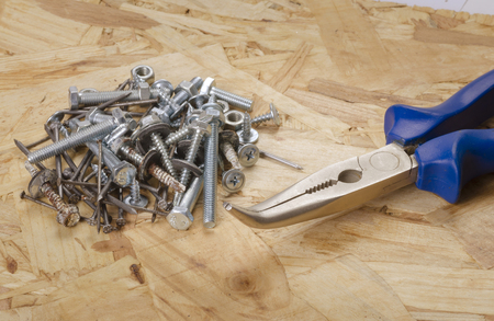 Building accessories. Pliers, bolts,screws, nails on particleboard