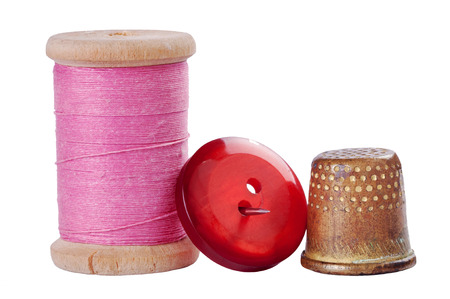 Old thimble, button and needle with pink thread on white with shadow Archivio Fotografico