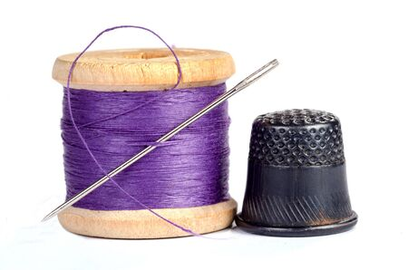 Old thimble and needle with thread on white with shadow