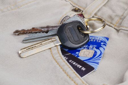 The keys and credit cards in the pocket of bright jeans close up