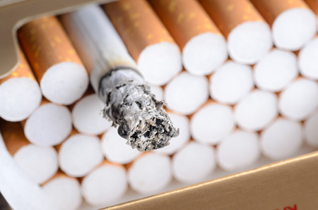 Cigarette with brown filter in the box with ash close up