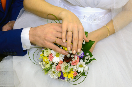 A newly wed couple place their hands on a wedding bouquet showing off their wedding bands.