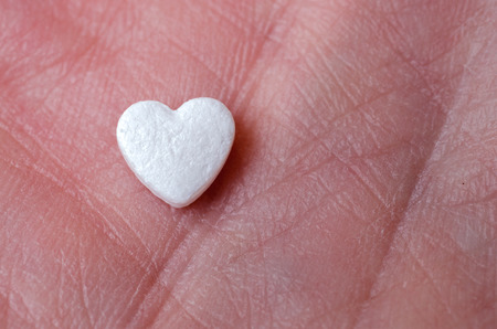 The tablet in the form of heart lay on the hand close up Archivio Fotografico