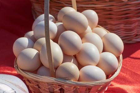 Chicken eggs in a wicker basket on red outdoor Archivio Fotografico