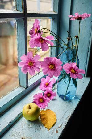 Flowers, apple and autumn leaf on the old windowsill
