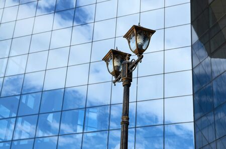 Urban street lamp against a glass wall with a reflection of the sky Archivio Fotografico