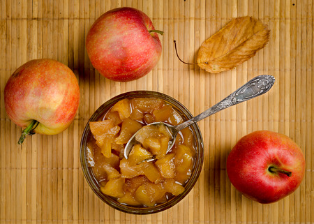 Apples and apple jam in a vase with a spoon top view