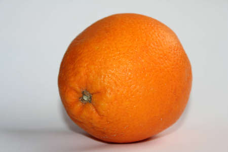 One ripe orange on white background