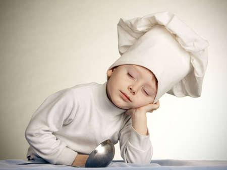 prodigio: The little boy in una tuta di cuoco. Il cuoco dorme