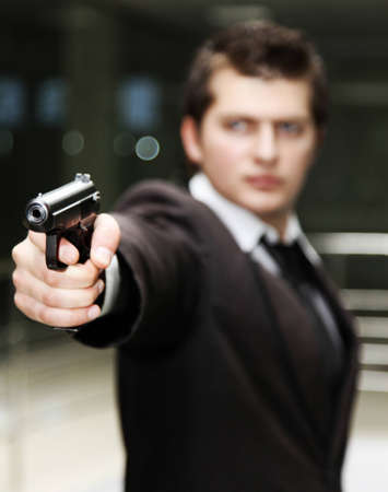 gunner: A bussiness man with a gun. (The focus is on the hand and gun) Stock Photo