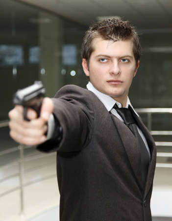 A bussiness man with a gun. (The focus is on the  face ) photo