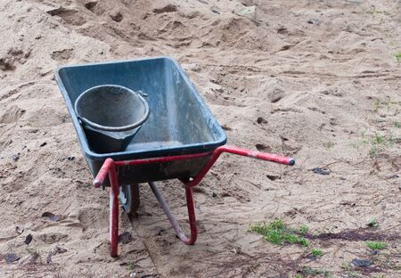 Wheelbarrow Rock and Sand Pile at an outdoor . photo