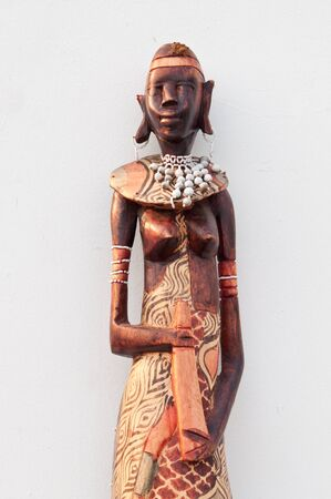 ebony wood: Wooden african figurine doll on white background