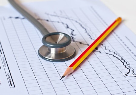 Stethoscope on  medical graph and pen.