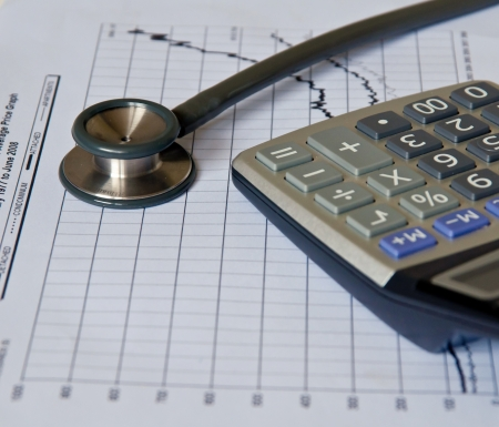 Stethoscope on  medical graph and calculator.