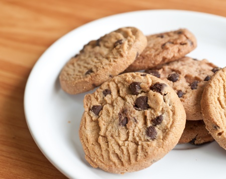 chocolate chips cookies in a dish on  the wood teble.