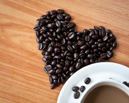 Concept of love with coffee beans on wood texture. photo