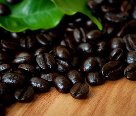 Roasted coffee  beans and coffee leaf  on wood texture. Stock Photo - 13452520
