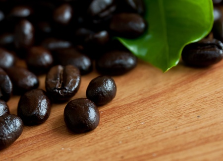 Roasted coffee  beans and coffee leaf  on wood texture. photo