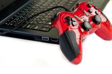 controlador de juego joystick de color rojo en la computadora portátil aislados en fondo blanco. Foto de archivo