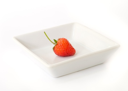 red ripe strawberries  on a white dish. photo