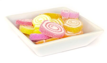 colorful  sweet fruit candy  on white dish . photo