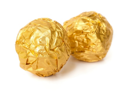 Two chocolate balls with almond  in a gold foil paper. photo
