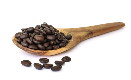 Coffee bean seed on wooden spoon isolated on a white background  photo
