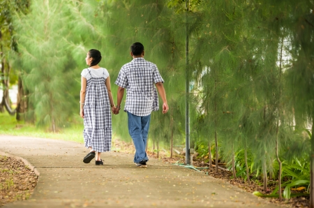 Portrait of  asian young couple in love  walking  in the  park  . photo