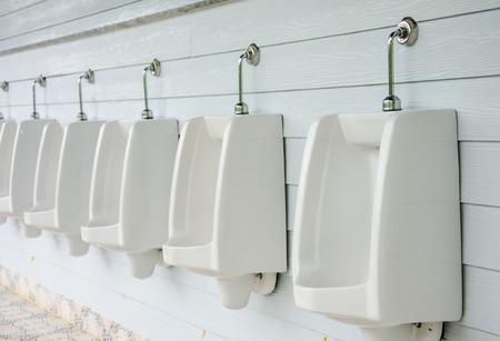 Closeup of  white urinals in men's bathroom.